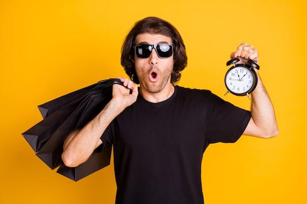 Foto di giovane uomo tenere borse negozio orologio orologio bocca aperta indossare t-shirt nera occhiali da sole isolato sfondo di colore giallo