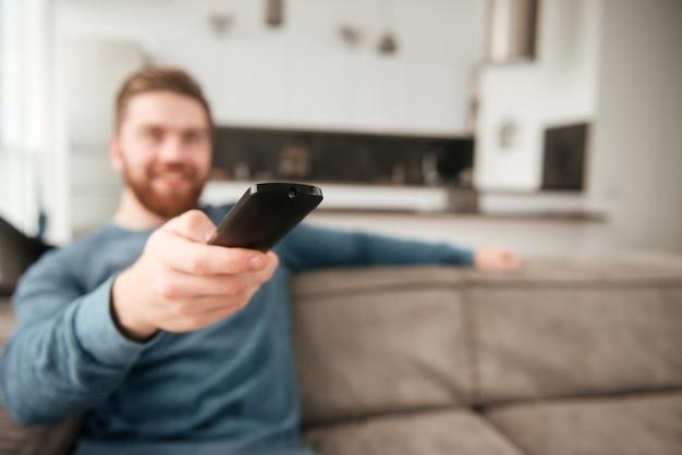 Foto di un giovane che tiene il telecomando mentre guarda la tv. focus sul telecomando.