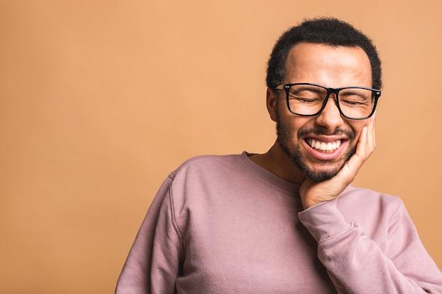Foto di un giovane uomo isolato su beige che soffre di un terribile dolore ai denti, che lo mostra vividamente sul viso, con aria turbata e angosciata.