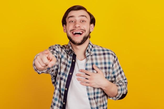 Foto di un giovane che ride di te che indica la telecamera e ti prende in giro o ti prende in giro contro il muro giallo