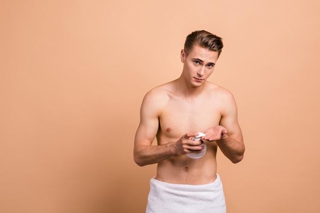 Foto del giovane che propone isolata sul beige pastello