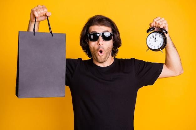 Foto di un giovane che mostra il quadrante della sveglia con il pacchetto del centro commerciale espressione sorpresa t-shirt occhiali da sole isolato sfondo di colore giallo