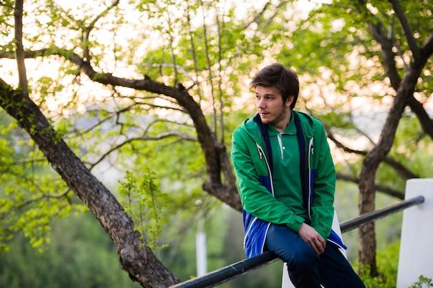 Foto di un giovane che per mezzo dello smartphone al tramonto