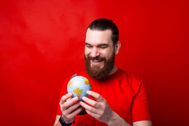 Foto del giovane con la barba che tiene il globo, giornata mondiale della pace