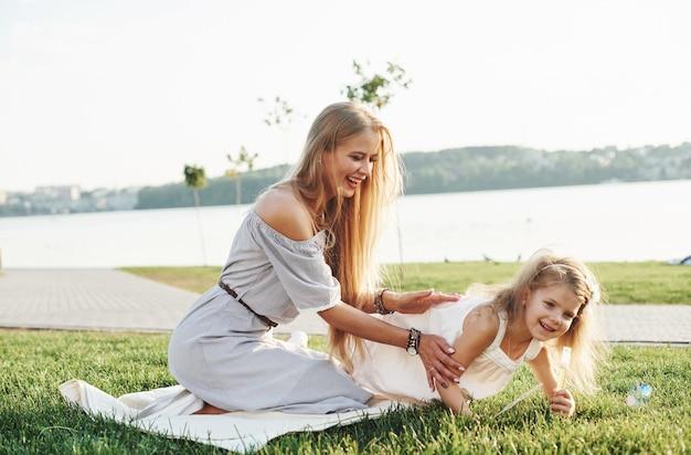 Foto di giovane madre e sua figlia che si divertono sull'erba verde con il lago sullo sfondo.
