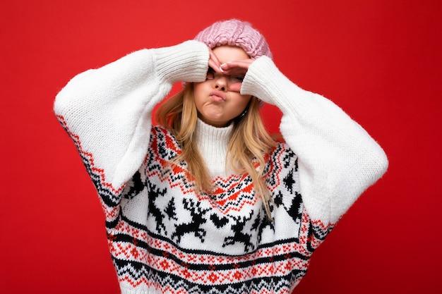Foto di giovane bella signora bionda felice positiva con emozioni sincere che indossa cappello lavorato a maglia rosa e pullover invernale