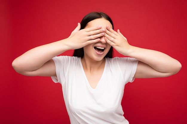 Foto di giovane bella donna sorridente felice positiva con emozioni sincere che indossa abiti eleganti isolati su sfondo con spazio copia e copre gli occhi con le mani