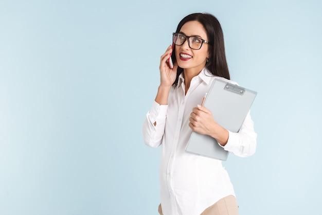 La foto di una giovane donna incinta di affari ha isolato la lavagna per appunti della tenuta che parla dal telefono cellulare.