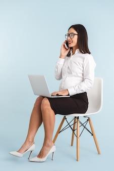 Foto di una giovane donna incinta di affari isolata utilizzando il computer portatile parlando dal telefono cellulare.