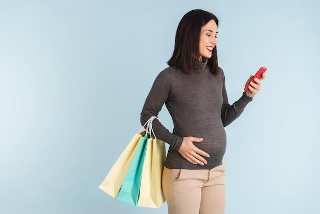 Foto di una giovane donna incinta isolata utilizzando il telefono cellulare tenendo i sacchetti della spesa.