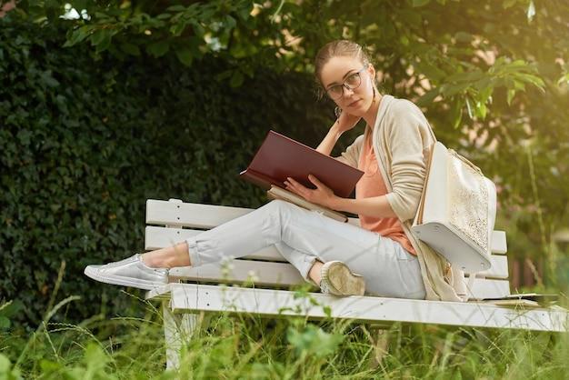 Foto di una ragazza giovane, carina e alla moda, che sta leggendo un libro sulla panchina del parco bianco. indossa abiti di colore chiaro: jeans, maglietta e cardigan. inoltre indossa uno zaino e occhiali da vista.