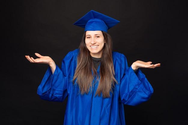 La foto della giovane donna dell'allievo in veste blu e fare il cappello di laurea non conosce il gesto
