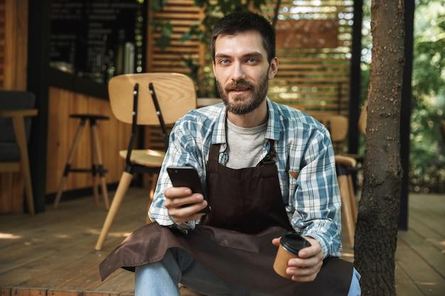Foto di un giovane cameriere che indossa un grembiule che utilizza lo smartphone mentre si lavora al bar o al caffè all'aperto