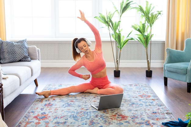 Foto di una giovane donna che si esercita a casa allunga i muscoli delle gambe e della schiena con un tutorial da internet