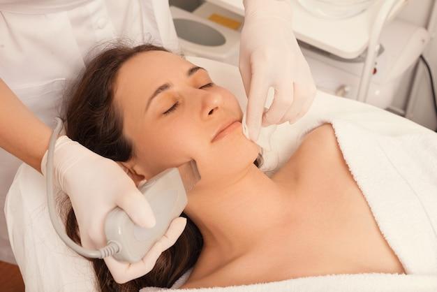 Foto di una giovane donna che fa un trattamento sulla pelle del viso con gli ultrasuoni