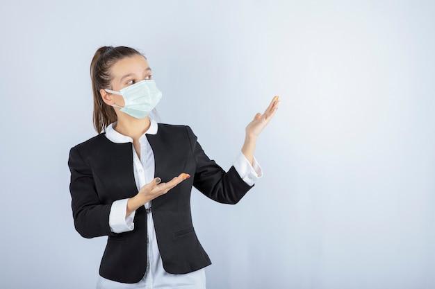 Foto di giovane donna in maschera che mostra qualcosa su sfondo bianco. foto di alta qualità