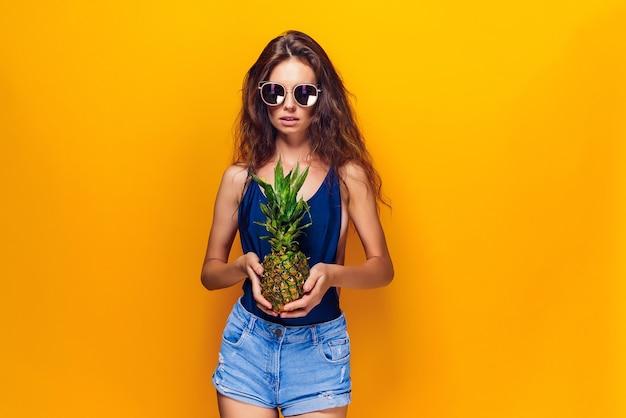 Foto di giovane donna in costume da bagno, pantaloncini blu, occhiali da sole isolati sopra l'ananas giallo della tenuta.
