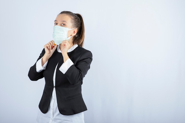 Foto di giovane donna che indossa maschera medica su sfondo bianco. foto di alta qualità