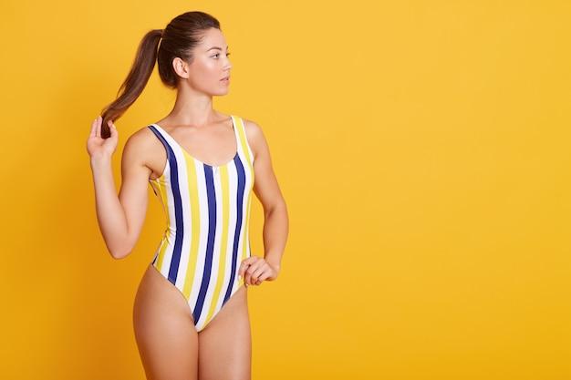 Foto di giovane donna con un corpo perfetto e costume da bagno spogliato skinwearing pulito, guardando da parte e tocca il suo ponitail, isolato su giallo. concetto di persone. copia spazio.