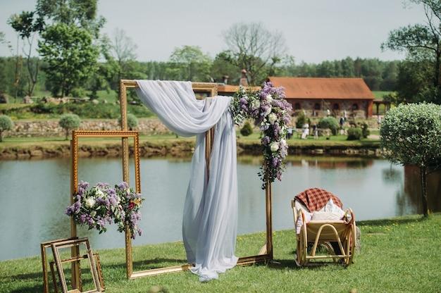 Zona fotografica a un matrimonio vicino al lago con una sedia. decorazioni per matrimoni estive per gli ospiti.