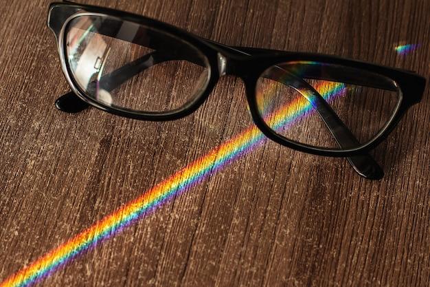 Occhiali fotocromatici su un tavolo di legno attraversano un raggio di sole scomposto in uno spettro arcobaleno. messa a fuoco selettiva