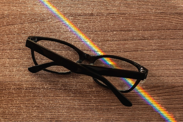 Occhiali fotocromatici su un tavolo di legno attraversano un raggio di sole scomposto in uno spettro arcobaleno.