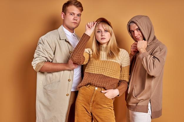 Gruppo fotogenico di giovani in posa in abito elegante e accogliente, riprese in studio