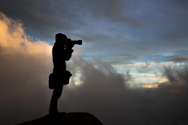 Fotografa la silhouette di un fotografo nella nebbia. in cima alla collina.