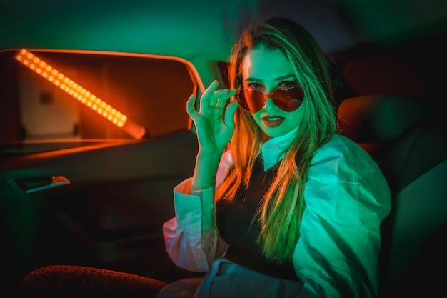 Fotografa con neon rossi e verdi nella parte posteriore di un'auto di una giovane donna bionda caucasica con gli occhiali a cuore
