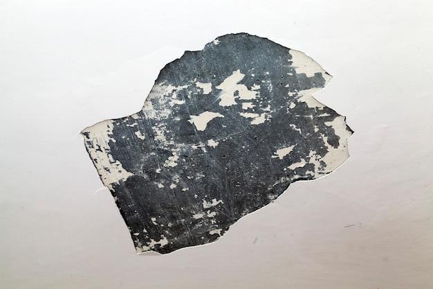 Primo piano fotografato di un intonaco rotto sul muro di un edificio. piccola profondità di campo