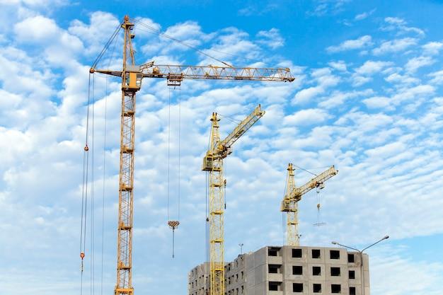Fotografato close-up gru edili durante la costruzione di un nuovo edificio di appartamenti a più piani, cielo blu e nuvole,