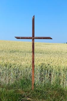 Primo piano fotografato della croce ortodossa arrugginita del vecchio metallo, situata all'aria aperta