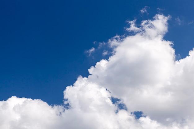 Le nuvole bianche del primo piano fotografate sono nel cielo blu, profondità di campo bassa