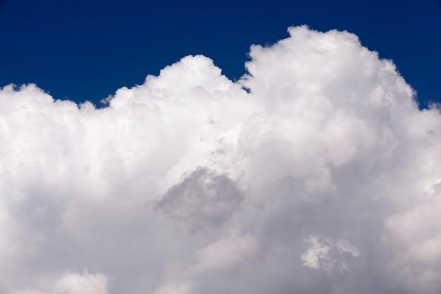 Le nuvole bianche fotografate del primo piano sono nel cielo blu, profondità del campo poco profonda