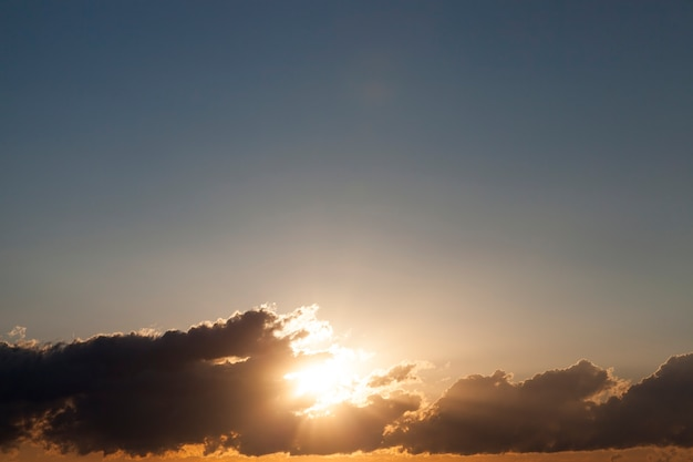 Parte fotografata di un cielo colorato con nuvole al tramonto, sole all'alba