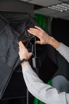 Il fotografo regola l'intensità della luce del softbox in studio. uomo che imposta attrezzatura fotografica che si prepara per un servizio fotografico.