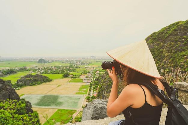 Fotografo donna asiatica con fotocamera reflex a ninh binh, vietnam