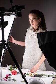 Fotografo in uno studio fotografico attrezzato che si prepara per le riprese