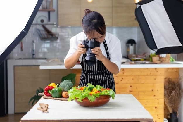 Il cibo del fotografo, le donne asiatiche sta prendendo le immagini dell'alimento il suo alimento in studio.