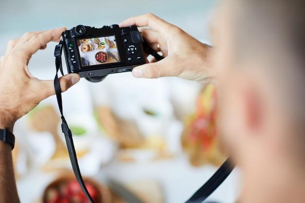 Fotografo holding digital camera