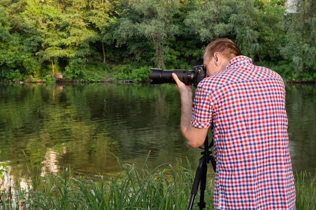 Il fotografo sta girando sulla riva del fiume, estate