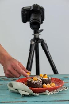 Fotografo che mantiene ciliegia gialla sul dessert, macchina fotografica nella priorità bassa