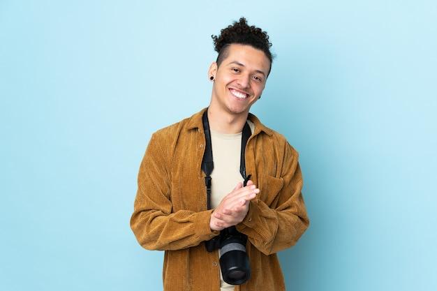 Uomo del fotografo sopra l'applauso blu isolato