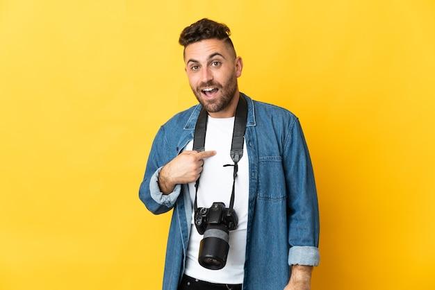 Uomo fotografo isolato su sfondo giallo con espressione facciale a sorpresa