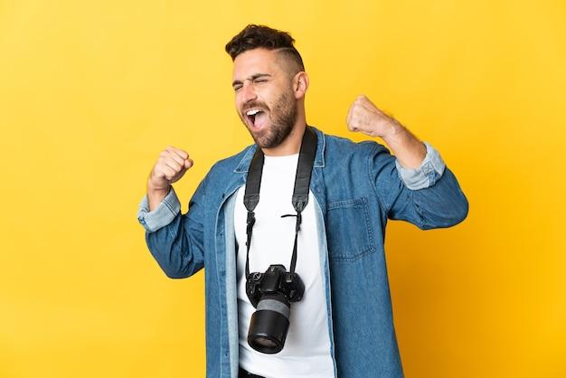 Uomo del fotografo isolato sulla parete gialla che celebra una vittoria