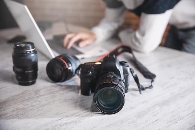 Uomo del fotografo con la macchina fotografica sulla scrivania