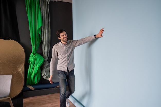 Il fotografo si prepara per le riprese in uno studio fotografico l'uomo cambia lo sfondo della carta in uno studio fotografico