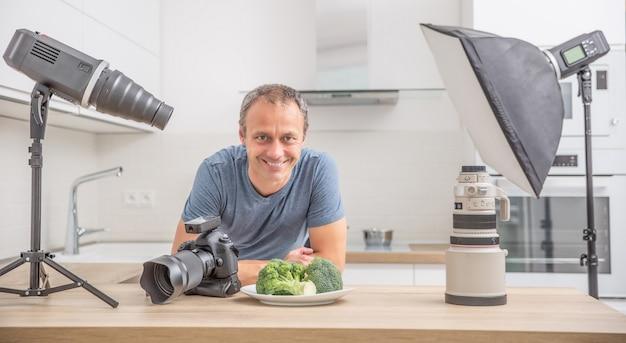 Fotografo professionista nella sua cucina studio con attrezzatura c