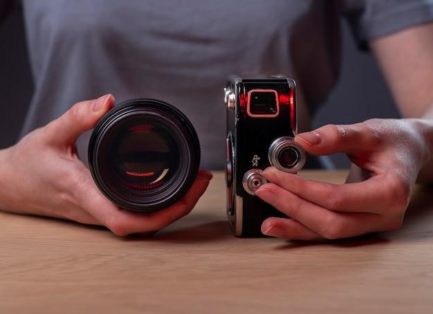 Fotografo che mostra due fotocamere, una vecchia vintage e una moderna lente digitale, primo piano.