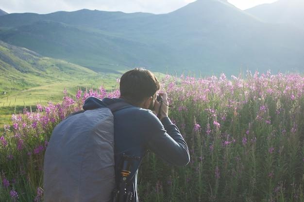 Il fotografo fotografa i fiori in montagna